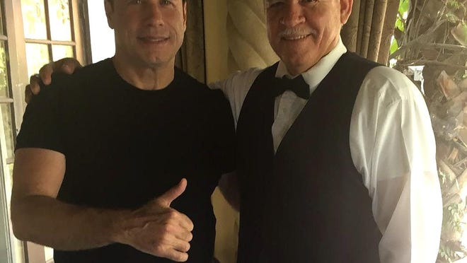 John Travolta, on left poses with Felipe Aspericueta, a busboy at Melvyn's restaurant in Palm Springs.