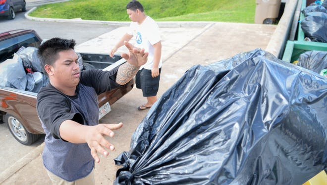 In this Nov. 25, 2016, file photo, Kevin Taisipic, left, and Brandon Duenas, offload household trash at the Harmon Residential Transfer Station. Some mayors said they're worried illegal dumping will increase in the wake of Typhoon Mangkhut.