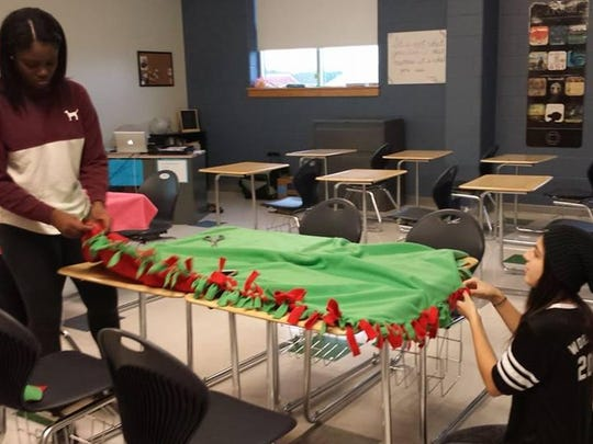 S. George's Tech students Maria Granston, left, and Tori Albanese make a fleece blanket to donate to children in hospitals for Project Linus.