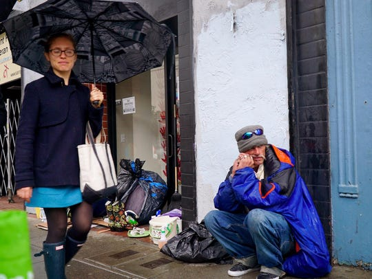 A woman averts her eyes as she walks past a homeless