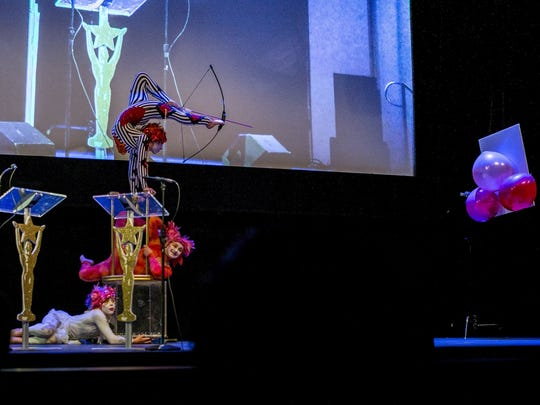 Corrinne Calhoun, at top, fires an arrow from a bow using her toed in a Le Petit Cirque performance at the Young Artist Awards in Los Angeles in March.