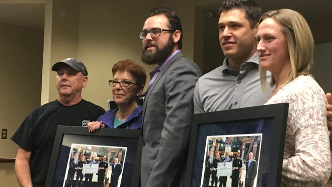 Fallen Wayne State police officer Collin Rose's parents, Randy and Karen Rose, standing next to Tigers pitcher Michael Fulmer and Tigers second baseman Ian Kinsler is next to Nikki Salgot, Collin's fiancee.