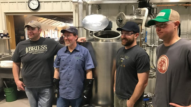 New Belgium and Odell brewers work on a collaboration beer. From left, Zach Baitinger of New Belgium, Scott Dorsch of Odell, Brent Cordle of Odell, and Christian Holbrook of New Belgium.