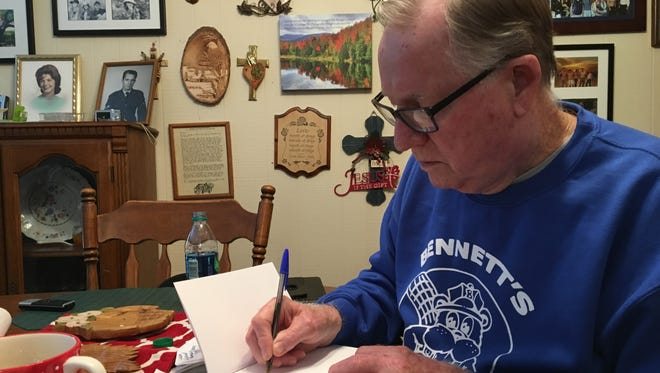 """Roger Evans inscribes a copy of his book, """"Mother is Coming Home."""""""