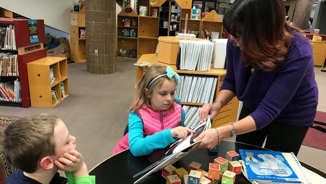 Karen Smith, head of children's services at the Livonia Public Library, shows a print and braille picture book from the new collection to Andrew Wilson, 6, and Lili Wilson, 8, of Livonia. The library also has print and braille alphabet blocks for children to explore.