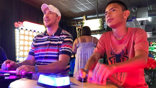 Malachi Duran (right) and his Big Brother, Alex Fuller, enjoy a game of Pac Man during an event at Dave & Busters on July 15, 2017.