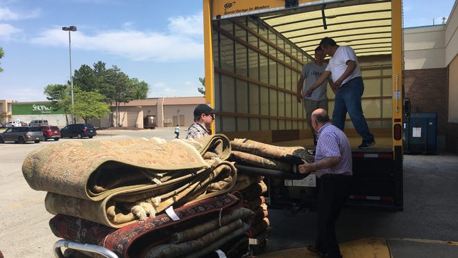 Shemiran Rugs owner Mohammad Farshchi, right, in purple, helps load rugs onto a truck from the Younkers Furniture Gallery in Bay Park Square. Farshchi had to remove the rugs after a pricing conflict arose with the liquidators that purchased Bon-Ton Stores Inc.'s assets.