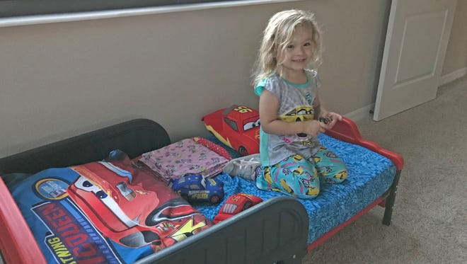 """Isabella was happy to find a """"Cars""""-themed bed when she arrived at her new house for the first time."""