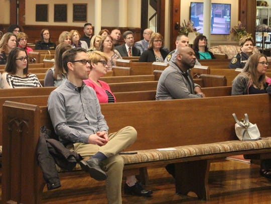 A crowd listens to Judge Teresa Ballinger speak during