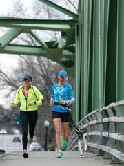 Pittsford residents Lori Harrington in yellow (who is originally from Boston) and running pal Patty van der Sloort with her dog Rosie go for a 10-mile run at Schoen Place in Pittsford. Both women are running the Boston Marathon on April 20.