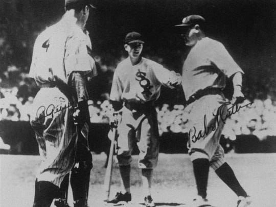 Babe Ruth, right, crossing home plate following a two-run