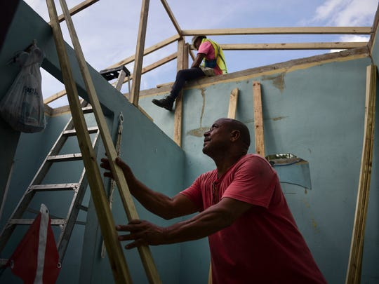 Pedro Deschamps helps workers hired by FEMA to carry out the installation of a temporary awning roof at his house, which suffered damage during Hurricane Maria, in San Juan, Puerto Rico, Wednesday, Nov. 15, 2017. A newly created Florida company with an unproven record won more than $30 million in contracts from the Federal Emergency Management Agency to provide emergency tarps and plastic sheeting for repairs to hurricane victims in Puerto Rico. Bronze Star LLC never delivered those urgently needed supplies, which even months later remain in demand on the island.