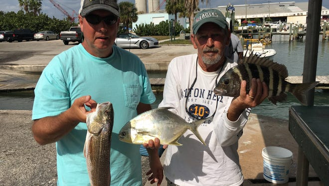 John and Gary hold a few of their catch of the day, redfish, pompano and sheepshead for dinner along with a few croakers on a beautiful fall morning.