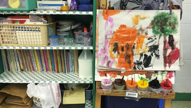 An easel and supplies in a preschool classroom.