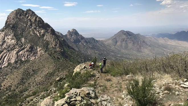 Hikers stop for a view of the Organ Needle, the highest peak in Organ Mountains-Desert Peaks National Monument, at nearly 9,000 feet.