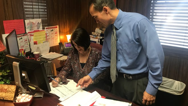 Sweetwater ISD Superintendent George McFarland, right, assists Laura Bedgood with paperwork in her office Wednesday, Aug. 9, 2017.