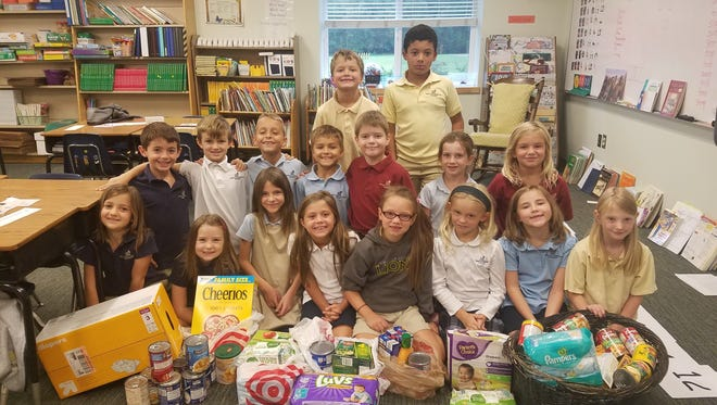 Terrie Gerolimatos' second-grade class at Asheville Christian poses with some of the donations they've gathers for victims of Hurricane Harvey.