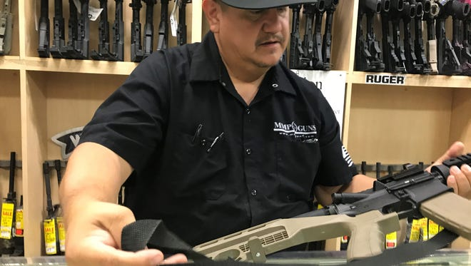 """Henry Escobar, gun manager at Mo Money Pawn shop, holds a AK-15 with a """"bump stock"""" attached to the back on Oct. 5, 2017. Interest in the device has spiked in Arizona since officials said Stephen Paddock used it during the Las Vegas shooting Oct. 1, 2017, which left 58 people dead and nearly 500 injured."""