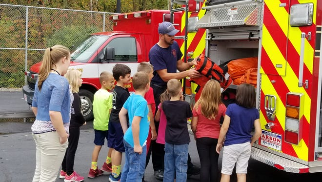 Galion firefighter and paramedic Lamar Newswanger shows water rescue equipment to students.