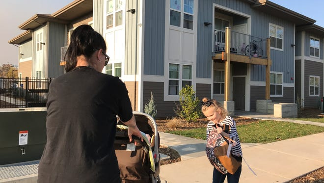 Chevette Chavez and her children, Chevelle, 6, and 3-week-old baby, Sparrow in the stroller, walk on Tuesday, Dec. 12, 2017 from school to their home at the Woodlands. Chevette said their two-bedroom home means the days of doubling up with family members is over and Chevelle can have her own bedroom.