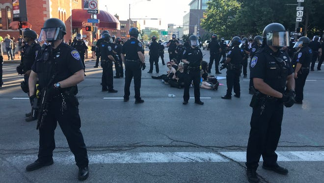 Rochester Police Department officers surround demonstrators who sat in the middle of Clinton Avenue following a rally on July 7, 2018.