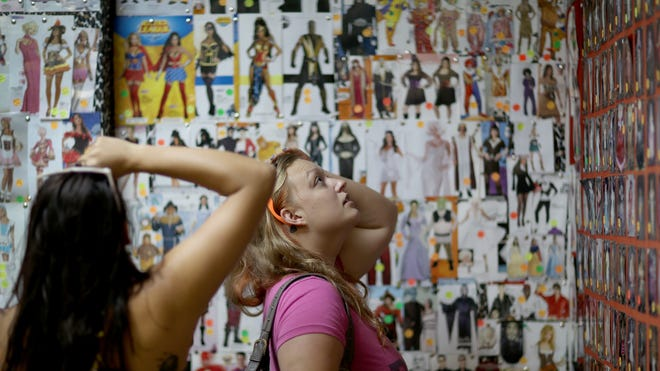 Amanda Kerr, right, and Sarah Helton shop for Halloween costumes at Dixon Costumes in Miami. Psychologists say the emphasis on sexy costumes for girls sends a troubling message about body images and the importance of appearance.