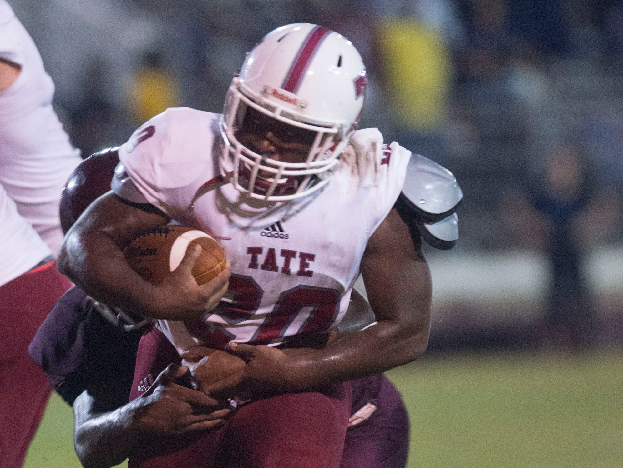 Tate High School running back, Corey Moorer, (No.20) gets wrapped up with a Pensacola High School defender during Friday night's preseason game at PHS.