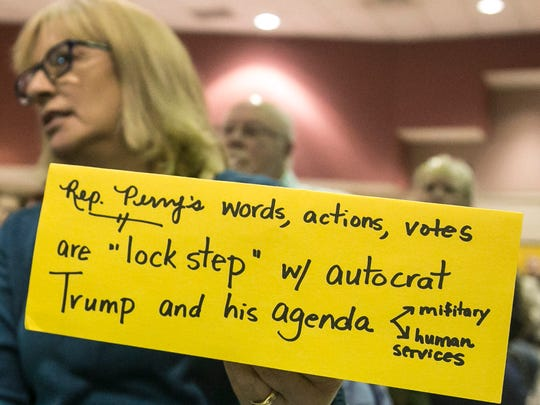 Liz Reilly, of Camp Hill, holds up her sign, after Rep. Scott Perry didn't fully answer a question regarding President Donald Trump, during his town-hall meeting  Saturday, March 18, 2017, at the Red Lion Area Junior High School. Amanda J. Cain photo