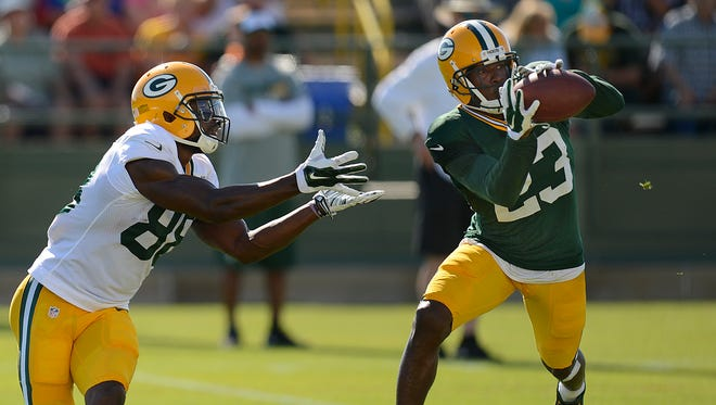 Green Bay Packers cornerback Damarious Randall (23) makes an interception in front of receiver Ty Montgomery (88) during training camp practice at Ray Nitschke Field on Thursday, Aug. 6, 2015.