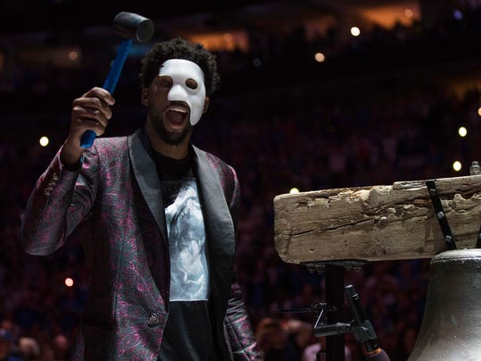 """Philadelphia 76ers' Joel Embiid comes out in a """"Phantom of the Opera"""" mask as he rings a Liberty Bell replica before Game 1 of the team's first-round NBA basketball playoff series against the Miami Heat, Saturday, April 14, 2018, in Philadelphia. (AP Photo/Chris Szagola)"""