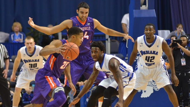 Evansville's Duane Gibson drives on Indiana State defender Everett Clemons on Wednesday in Terre Haute. Watching the action are Purple Ace David Howard and Sycamore T.J. Bell (42).