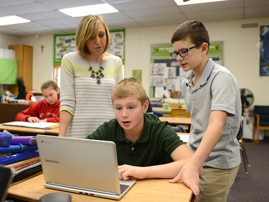 Teacher Abbie Withbroe works with students Ben Laskowski, right, and Drake Anderson, during sixth-grade social studies class Wednesday at St. John the Baptist Catholic School in Howard.