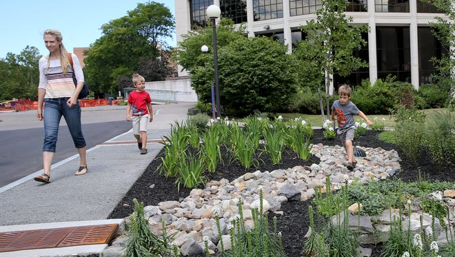 Luise Farrell walks with her sons Matias, 6 and  Robert , 4 from Brighton along the new porous concert sidewalk and water collection system at the RMSC.