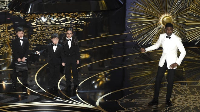 FILE - In this Sunday, Feb. 28, 2016 file photo, host Chris Rock, right, gestures to three unidentified children portraying auditors in a skit at the Oscars at the Dolby Theatre in Los Angeles. Rock's skit ignited an outcry from Asian-Americans and others angered by its stereotyping and, more broadly, frustrated by how non-black minorities are portrayed - or ignored - by Hollywood, especially movie studios. The response also has illuminated the gap between African-Americans, who have made on-screen gains, and the lagging progress by other minorities including Asian-American, Latinos and Native Americans. (Photo by Chris Pizzello/Invision/AP, File)