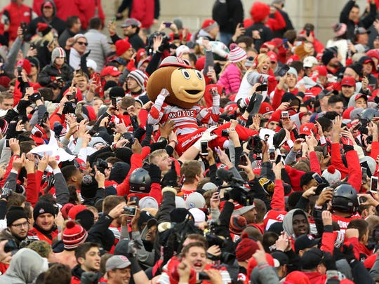 Brutus Buckeye crowd-surfs as fans surge onto the field following the win over the Michigan Wolverines at Ohio Stadium. Ohio State won 30-27.