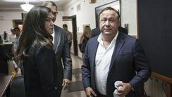 Infowars host Alex Jones, right, is being sued by Greek