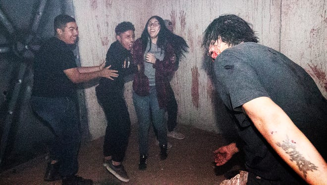 Isabel Flores, 18, right, and friends react to creatures lurking in the darkness inside one of the enclosures at the Town Square Media KLAQ Haunted House at Desert Warrior Paintball at 13900 East Montana Ave. in the Montana Vista Area. This year's edition consists of a zombie apocalypse theme in an outdoor maze of rooms and tunnels.