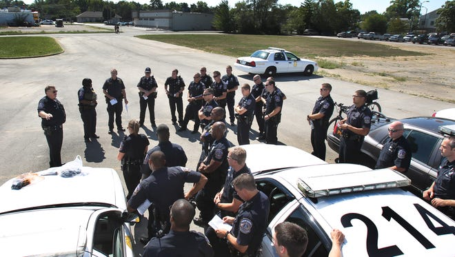 Indianapolis Metropolitan Police Department Lt. Terry Eden, left, conducts roll call in a parking lot Sept. 24, 2013.