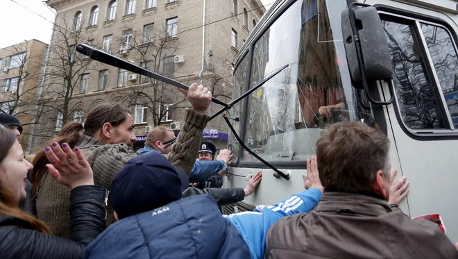 Pro-Russia supporters attack a police bus  near the regional government building in Kharkiv, Ukraine, on April 7.