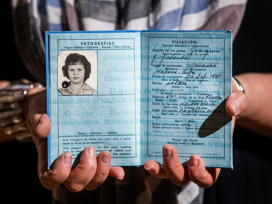 Yrene Waldron holds her Cuban passport with a photo of her as a young girl in her home in Brandywine Hundred on Monday evening. Waldron fled Cuba with her brother when she was 10 years old and he was nine.