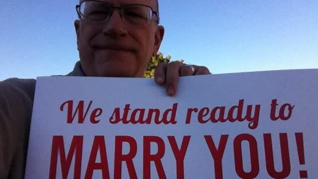 United Church of Christ pastor Vernon Meyer holds a sign that clergy are using to signal their availability for wedding services at county offices around Arizona.