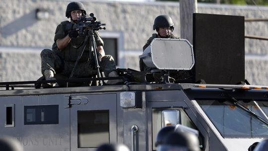 A police tactical team moves in to disperse a group of protesters in Ferguson, Mo. on Aug, 9, 2014, that was sparked by the shooting of Michael Brown.
