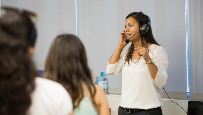 Erika Martinez, student advisor for the international welcome center at Centennial High School, talk with parents and students about the language learning computers and headsets. Monday Aug. 28, 2017.