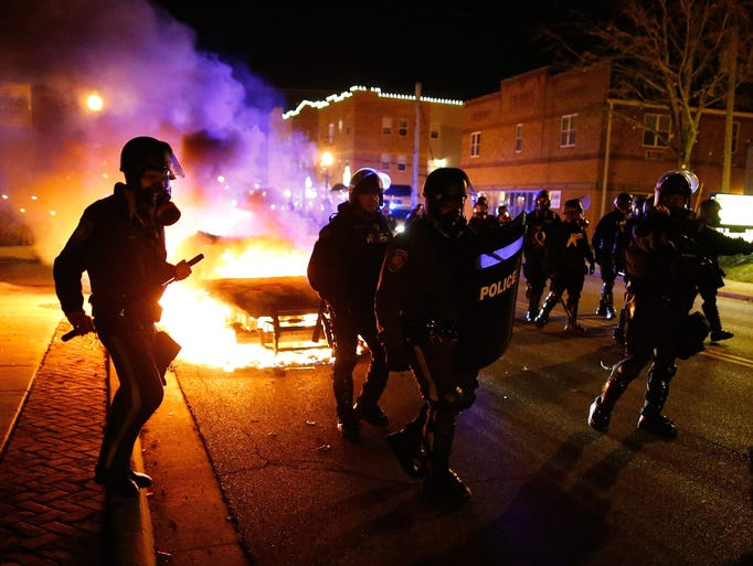 Police in riot gear move past a vehicle that continues