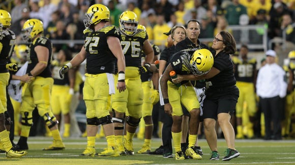 Sep 5, 2015; Eugene, OR, USA; Oregon Ducks quarterback Vernon Adams Jr. (3) is helped by the training staff following a late hit in the fourth quarter against the Eastern Washington Eagles at Autzen Stadium. Mandatory Credit: Scott Olmos-USA TODAY Sports