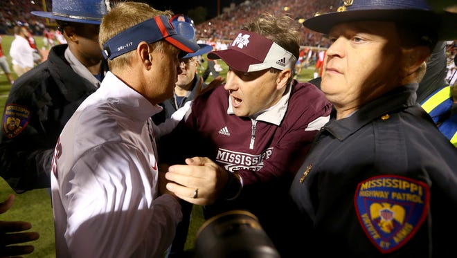Ole Miss coach Hugh Freeze, left, and Mississippi State's Dan Mullen meet at midfield following the 2015 Egg Bowl. The two meet again this Saturday.