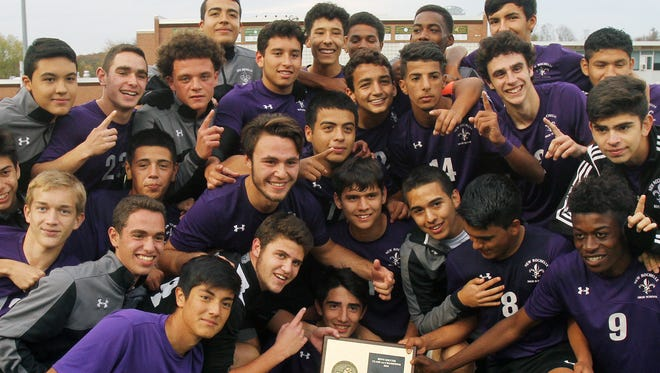 New Rochelle payers celebrate with the section 1 plaque after defeatingd Arlington 3-0 in the boys soccer Section 1 Class AA championship game at Lakeland High School in Shrub Oak High School Oct. 29, 2016.