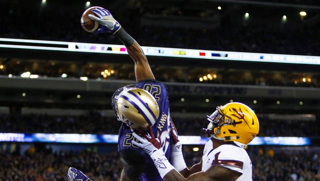 Washington defensive back Kevin King makes a one-handed interception in the end zone on a pass intended for Arizona State's N'Keal Harry during a November game at Husky Stadium.