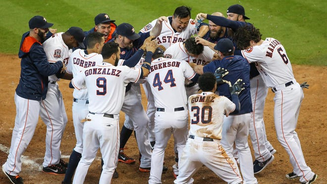 Jason Castro is in the middle of a celebratory scrum after his walk-off home run in the 10th inning beat the Dodgers on Sunday.
