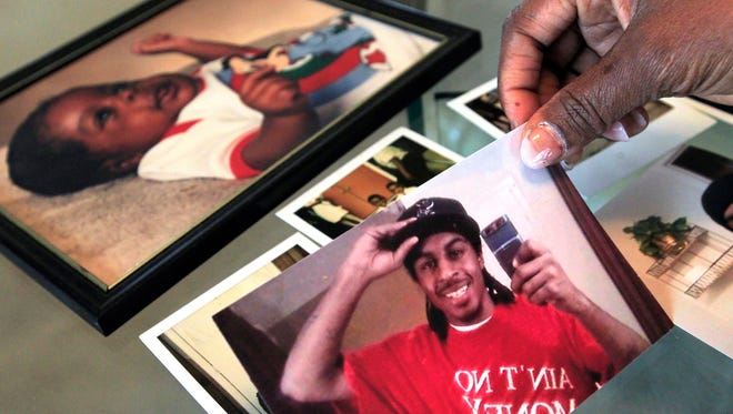 """Debra Watson of Indianapolis looks over photos of her son, Thomas """"DJ"""" Keys, a local rapper who was slain in 2012."""